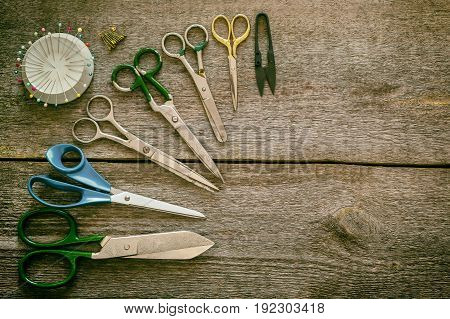 Creative image of sewing accessories for needlework and sewing hobby retro style on old wooden surfaces