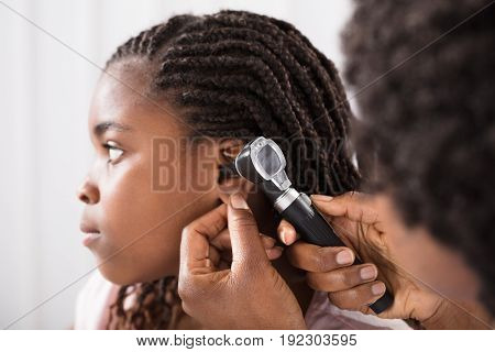 Doctor Using Otoscope Instrument To Check Girl's Ear In Hospital