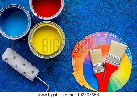 Set of tools for painting on blue wooden desk background top view.