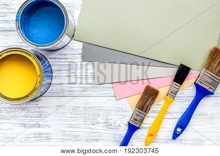 Colorful paints and brushes on grey wooden desk background top view copyspace.