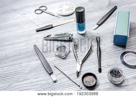 manicurist work place with manicure set and nail polish for hands care on gray wooden background