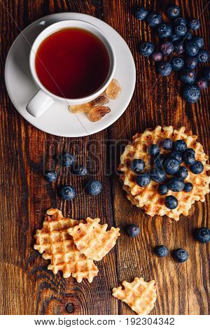 White Cup of Tea with Blueberries and Whole and Broken Belgian Waffles on Wooden Background. Vertical Orientation.