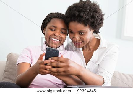 Mother And Daughter Sitting On Couch Looking At Smart Phone