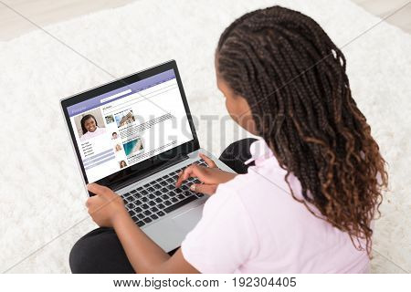 Girl Sitting On White Carpet Browsing Social Site Using Laptop At Home