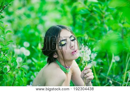 Woman With Fashionable Makeup And Beads In Green Leaves