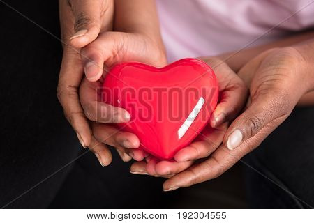 Elevated View Of Mother's And Daughter's Hand Holding Red Heart
