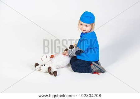 small smiling boy in blue doctor uniform playing vet with toy animal of donkey in medical hospital isolated on white background medicine and healthcare copy space