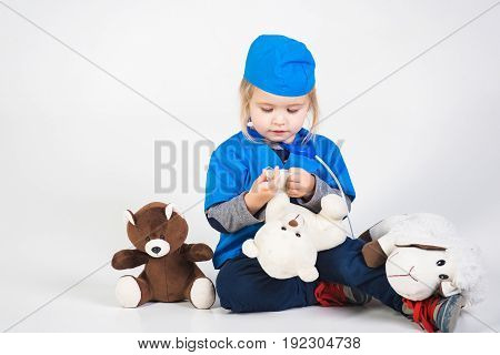 child or small boy in blue doctor uniform playing vet with toy animal of donkey and bear in medical hospital isolated on white background medicine and healthcare copy space