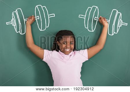 Smiling Girl Lifting Weights Drawn On A Green Chalkboard
