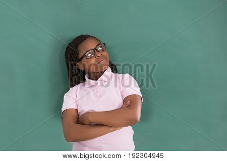 Close-up Of Thoughtful African Girl Standing Against The Green Chalkboard In Classroom