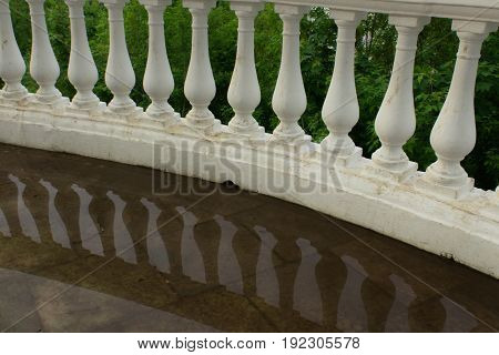 Balusters of rounded handrails with reflection in water photo