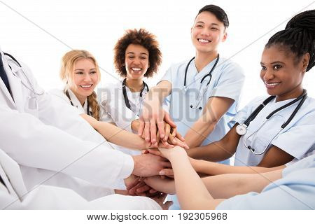 Group Of Happy Doctors Stacking Their Hands Against White Background