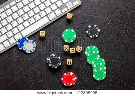 Online poker. Chips and the dice nearby keyboard on grey stone table top view.