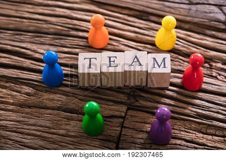 High Angle View Of Team Word On Wooden Block With Multi Colored Sculpture
