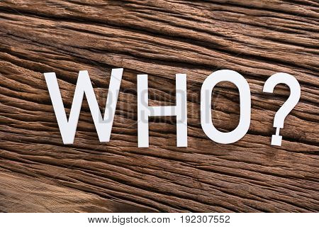 Elevated View Of WHO Text With Question Mark Sign On Wooden Table