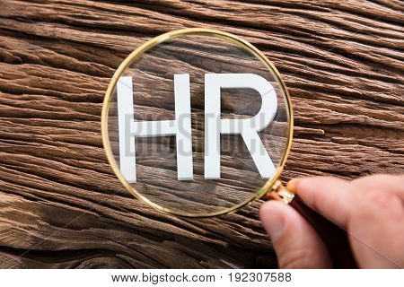 Elevated View Of A Person Looking At HR Text Through Magnifying Glass On Wooden Table