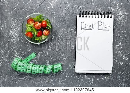 Notebook for diet plan, salad and measuring tape on grey stone table top view mock up.