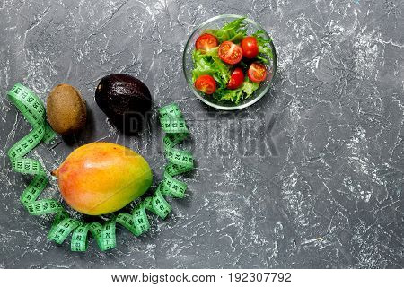 Healthy diet. Salad with fresh products and fruits mango, mangosteen, kiwi and measuring tape on stone table top view.