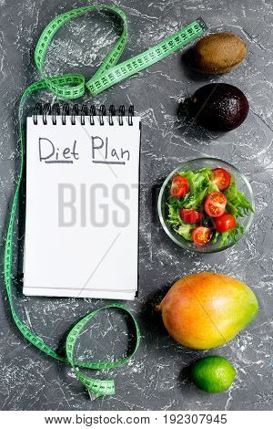 Slimming. Notebook for diet plan, fruits salad and measuring tape on grey stone table top view mock up.