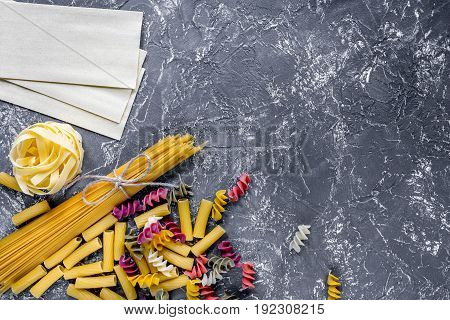 Assortment of different shape italian pastas on grey stone table top view copyspase.