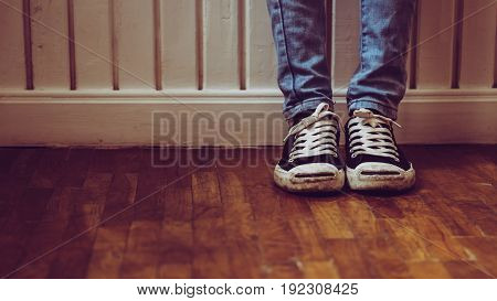 Looking down on feet stand alone in house