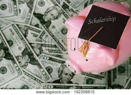piggy bank with scholarship graduation cap on money