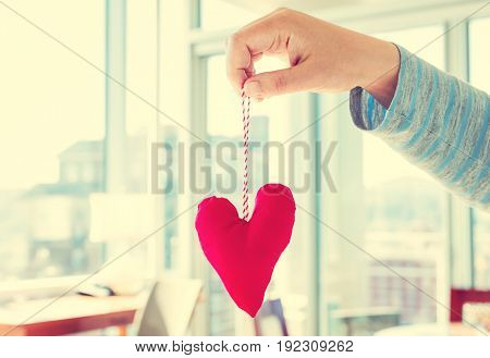Woman holding a heart cushion in a bright room