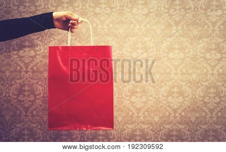 Woman holding a red shopping bag on an elegant background
