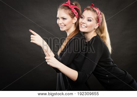 Information and messages. Two blonde pin up retro style women showing something interesting by their fingers. Vintage girls body language.