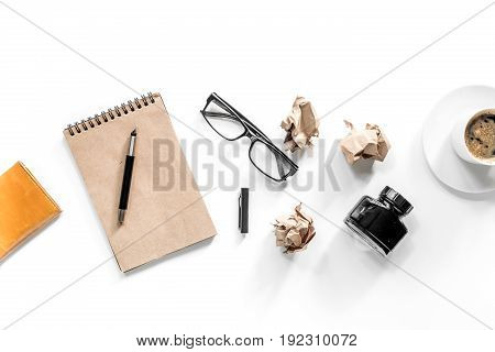 Writer concept. Vintage notebook, crumpled paper and glasses on white background top view.