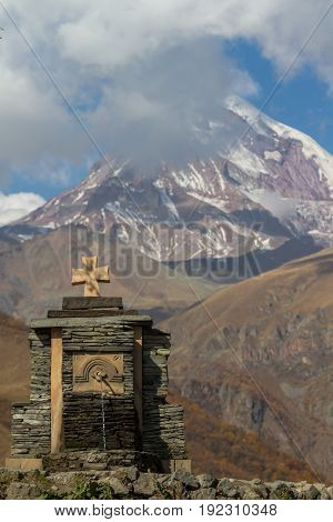 A Water Spring Near The Old Trinity Church, And The Snow Capped Mountain Of Kazbegi