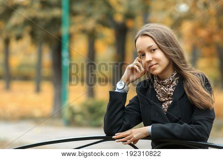 A Young Beautiful White Girl With A Watch On Her Hand Is Sitting On A Vintage Bench In The Golden Au