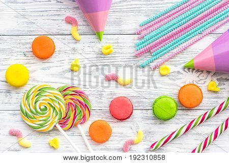 Sweets for birthday including lollipop and macarons on wooden desk top view.