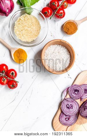 homemade paella ingredients composition with rice, tomato, onion on white kitchen table background top view mock-up