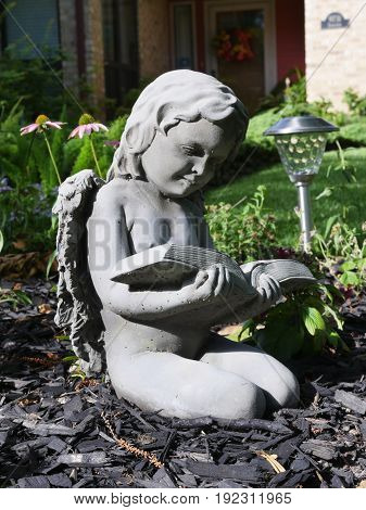Small angel statue kneeling reading a book