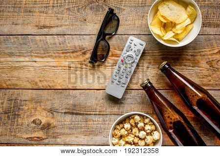 home party with TV watching, snacks, pop corn, chips and beer on wooden background top view mock up