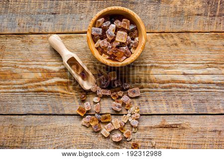 lumps of brown sugar on gray wooden table background top view mock up