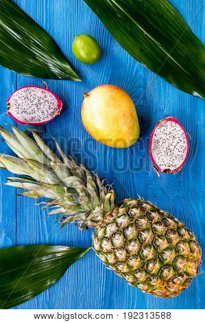 Pineapple, dragonfruit and lime on blue wooden desk background top view.