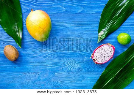 Exotic fruit meal. Dragonfruit, mango, kiwi, lime on blue wooden table background top view.
