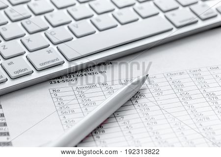 Business report preparing with pen and keyboard on office desk background