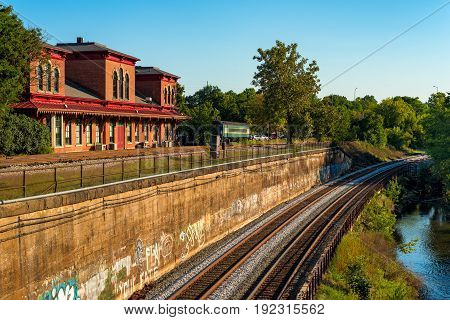 KENT OH - SEPTEMBER 4 2016: The old train depot recently a popular restaurant stands over the mainline tracks running along the Cuyahoga River at lower right.