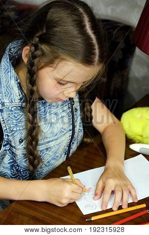 the child sits at the table and draws a picture