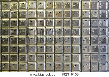 Wall full of rows of old shiny metal post office boxes
