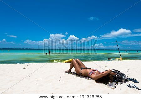 BORACAY, WESTERN VISAYAS, PHILIPPINES - MARCH 27, 2017: Woman lying down at White Beach during a sunny day.