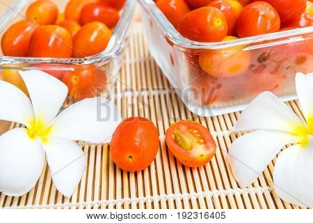 Fresh tomatoes with white plumeria flowers in glass box on the table