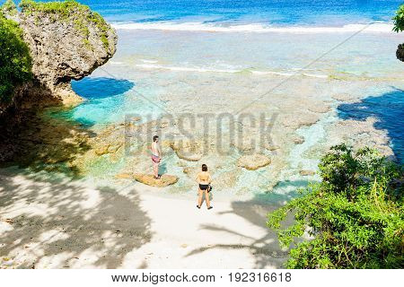 Alofi, Niue - May 30, 2017; Man and woman in swimwear stand by tropical patterns and colors of coral reef and sea on small isolated beach in editorial image.