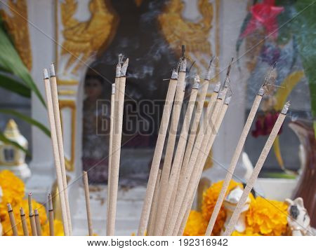 burning incense sticks on blurred background of spirit house with waving smoking