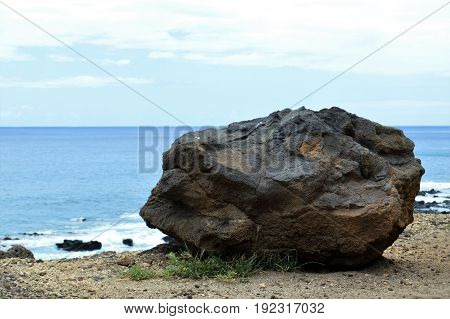 big rock in front of ocean water