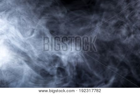 Smoke from a Vape with light effects on a black background. The image is an abstract texture with copy or text space. It has patterns showing movement and depicts a spooky mood with a Halloween theme.