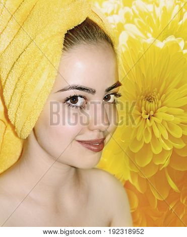 photography with scene of the beautiful girl with towel on head on background of the yellow chrysanthemum